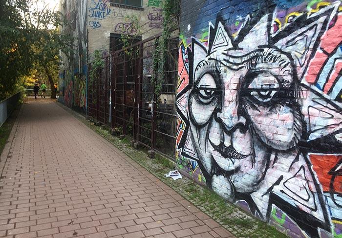 Graffiti mit großem schwarz-weißen Sonnen-Gesicht, im Hintergrund Läufer