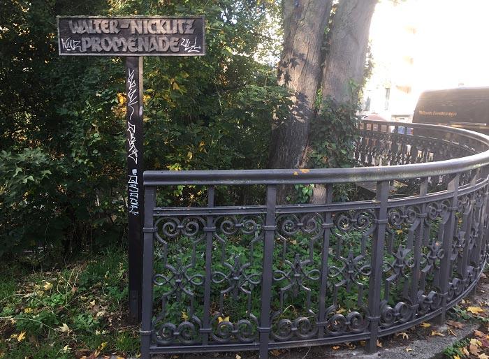 Schild Walter-Nicklitz-Promenade neben schmiedeeisernem Zaun mit Ornamenten
