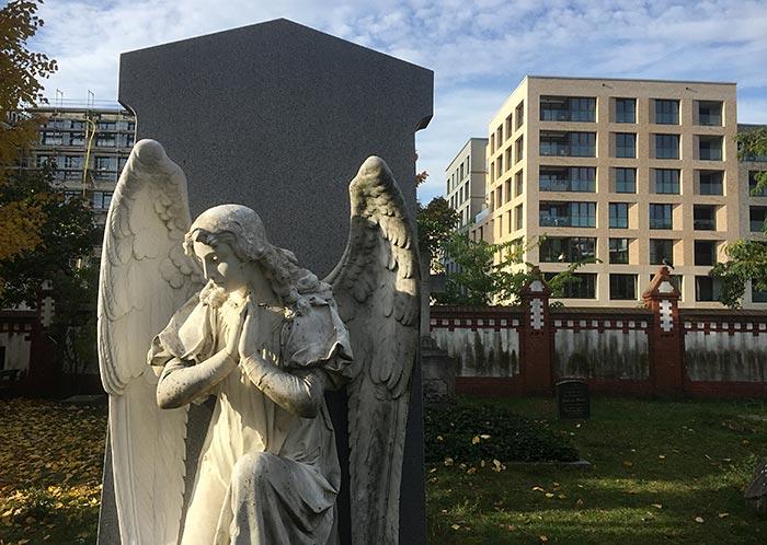 Engel-Statue auf dem Invalidenfriedhof, dahinter Neubauten