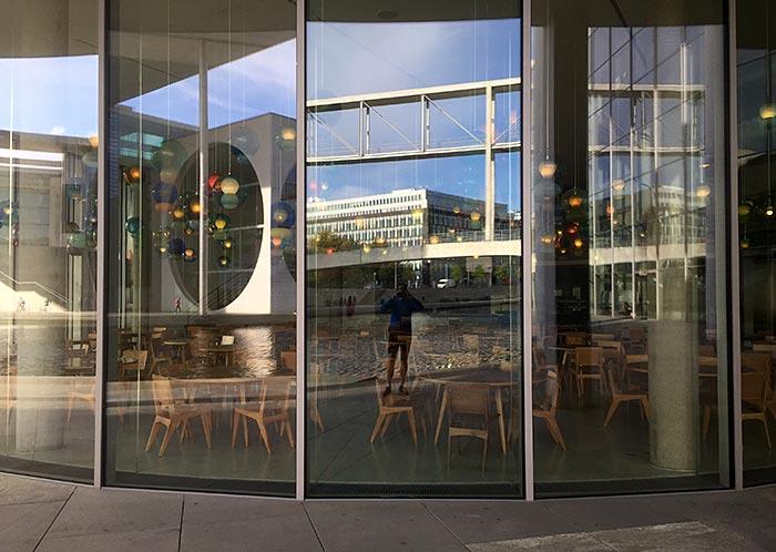 Läufer spiegelt sich in Glasfassade des Paul-Löbe-Hauses