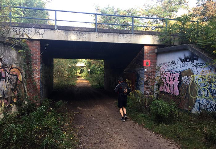 Läufer unter einer kleinen Eisenbahnunterführung