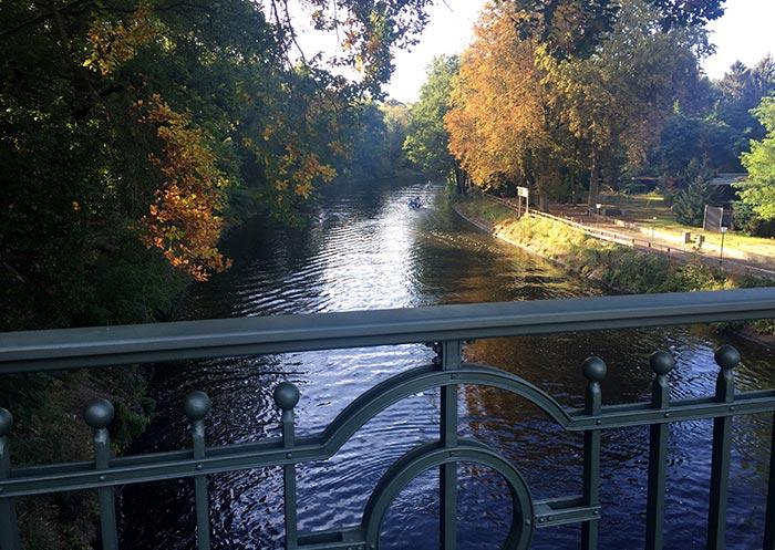 Blick von einer kleinen Brücke auf das Wasser mit einem Boot