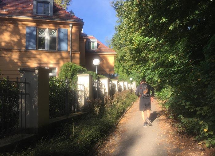 Läufer auf schmalem Weg neben imposanten alten Villen