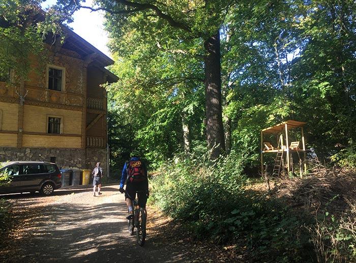 Altes Forsthaus mit Läufer und Radbegleiter im Vordergrund