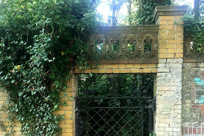 Alte efeuberankte Mauer mit kunstvollen Verzierungen und kleinem schmiedeeisernen Tor