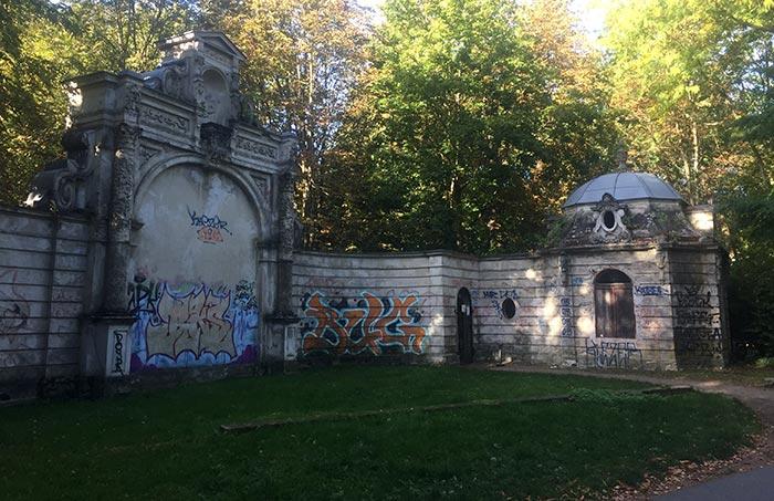 Mauer mit prunkvollem Portal, von Graffiti beschmiert