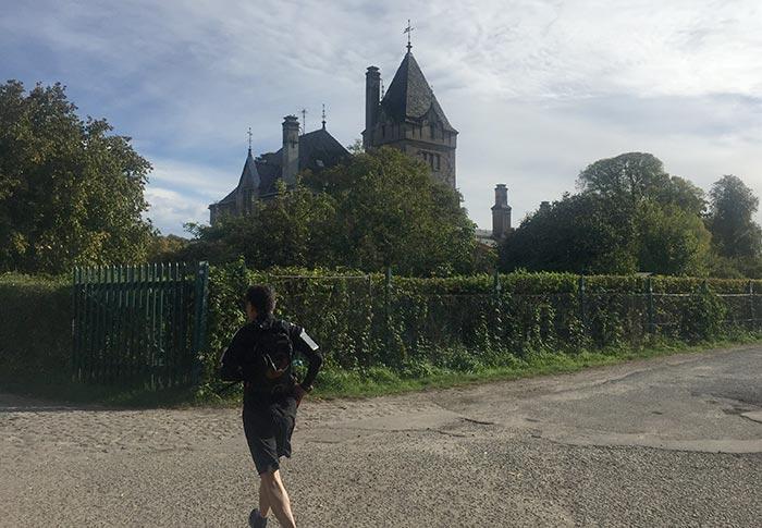 Läufer vor Hecke, dahinter ein altes, burgähnliches Gebäude