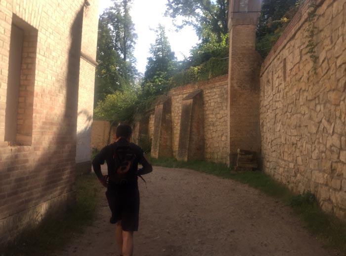 Läufer läuft durch Gang zwischenaltem Gebäude und hoher Mauer