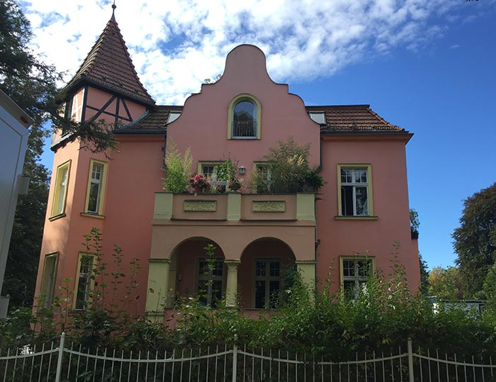 Rosa-gelb gestrichene Villa mit üppig begrüntem Balkon