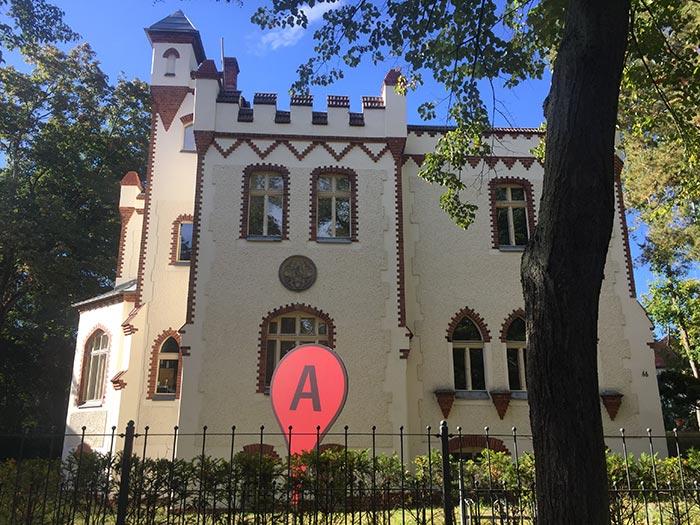 """Beeindruckendes altes Gebäude mit mannshohem rotem Google-Pin mit """"A"""" im Vorgarten"""