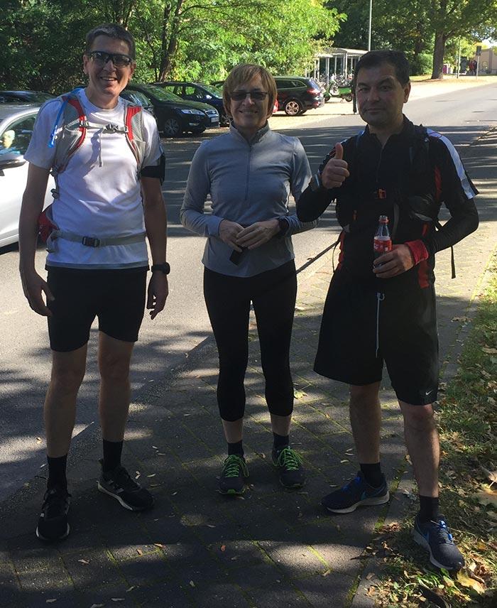 Läuferin und zwei Läufer mit Trink-Rucksäcken machen Pause