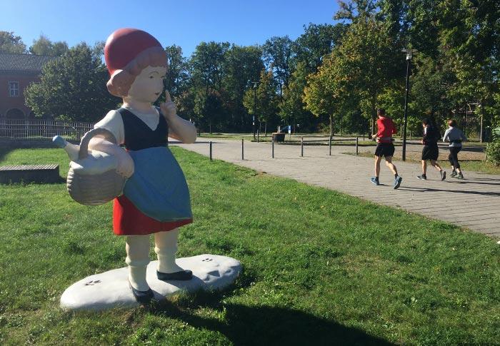 Menschengroße Rotkäppchen-Plastik, im Hintergrund laufen Läufer vorbei