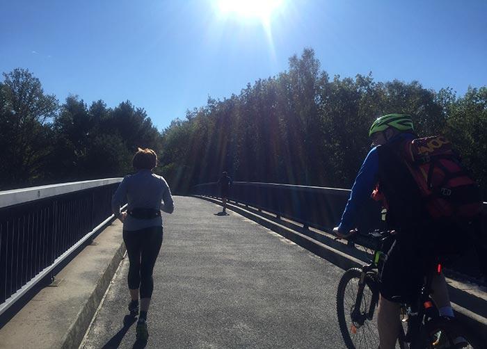 Läuferin und Radbegleiter auf Brücke