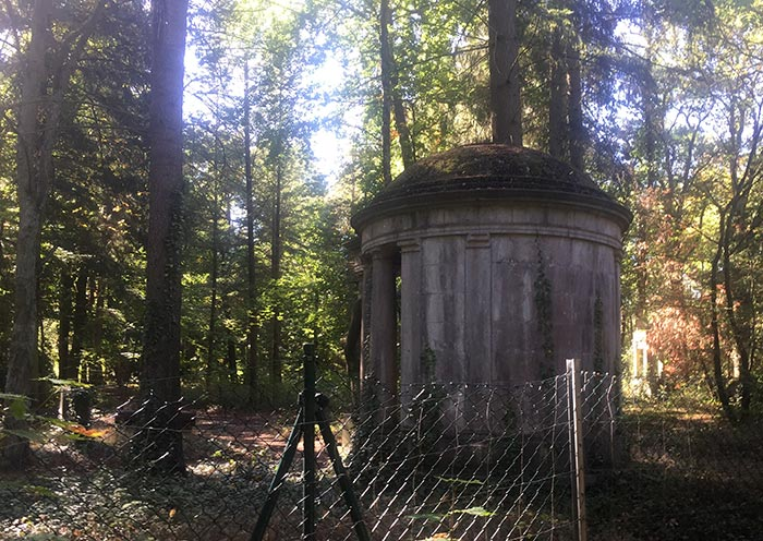 Alte tempelähnliche Grabstätte hinter einem Maschendrahtzaun im Wald