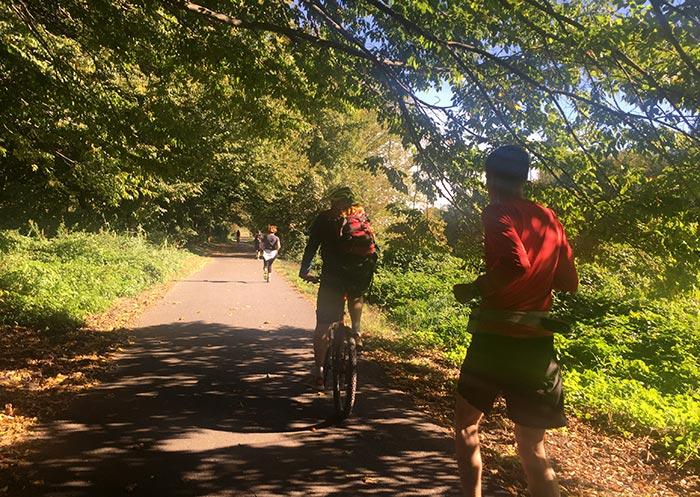 Läufer, Radbegleiter, Läuferin in weiten Abständen auf Weg am Teltowkanal