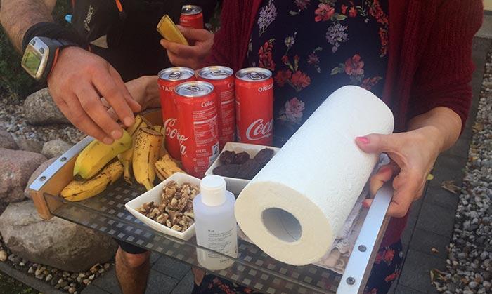 Frau hält Tablett mit Bananenstücken, Nüssen, Datteln, Coladosen und Küchenrolle