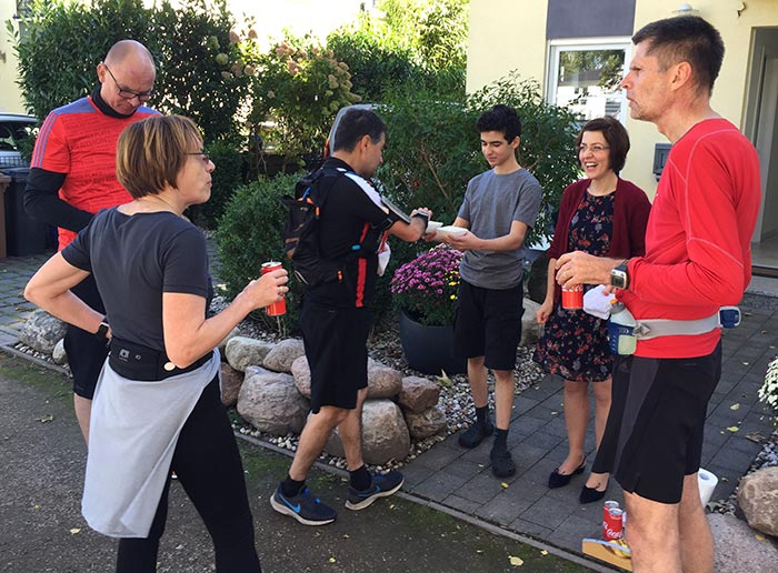 Läuferin und Läufer werden vor Haus verpflegt