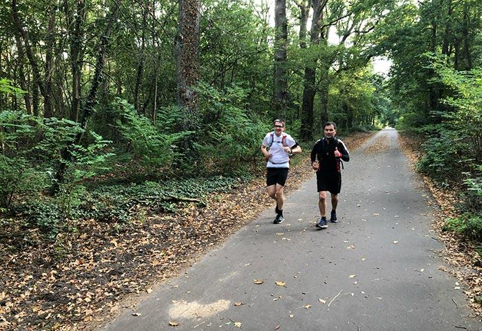 Zwei Läufer mit Trink-Rucksäcken auf schmalem Asphaltweg im Wald