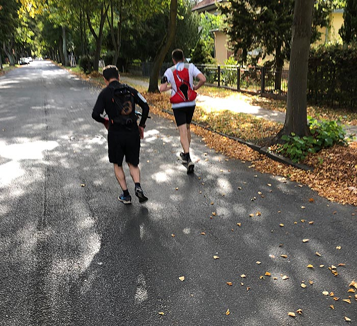 Läufer mit Trink-Rucksäcken laufen auf Straße