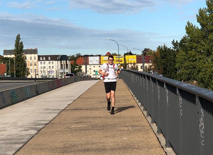 Läufer läuft über Brücke