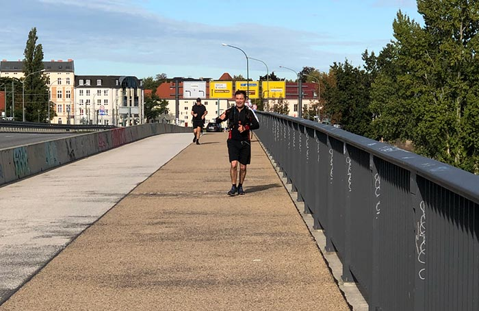 Läufer läuft über Brücke, hebt Daumen hoch