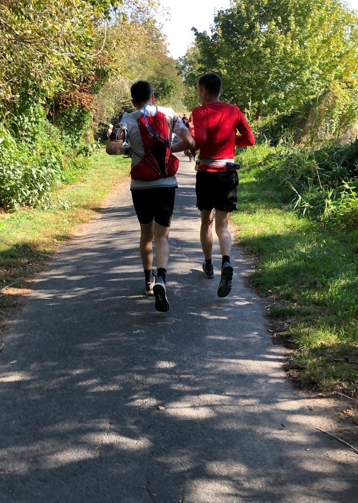 Läufer auf schmalem Asphaltweg