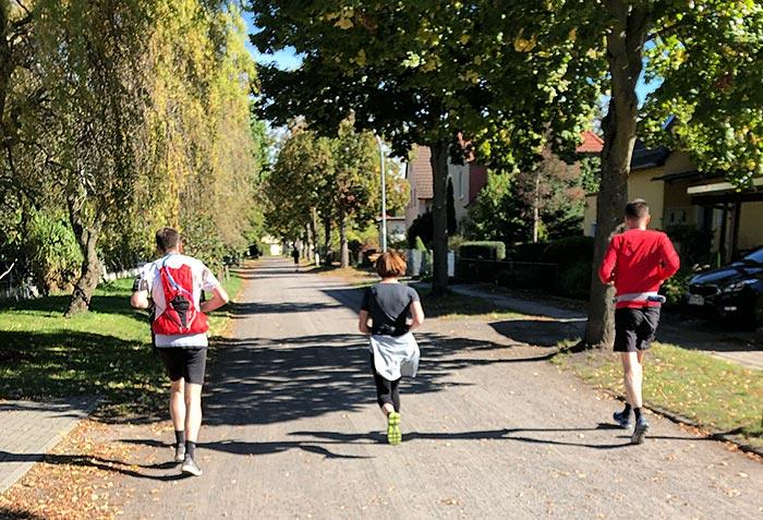 Läufer, Läuferin und eoin weiterer Läufer laufen nebeneinander auf einer kleinen Straße