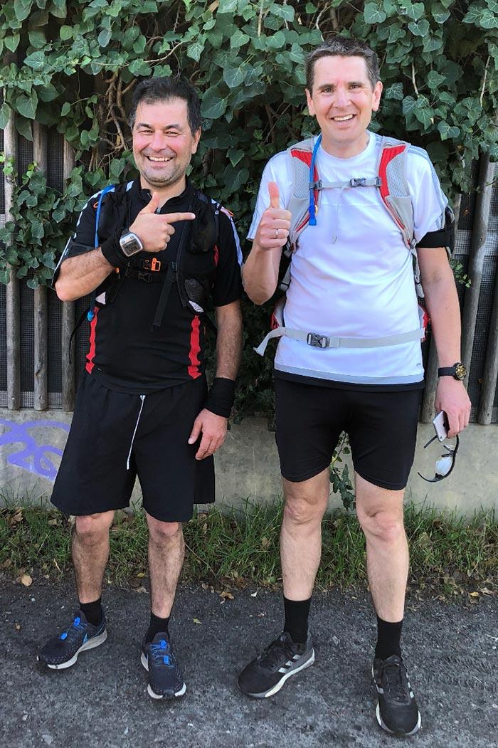 Lächelnde Läufer stehen vor Efeuwand und heben Daumen, lniker Läufer zeigt auf rechten Läufer
