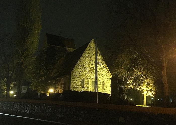 Dorfkirche Alt-Buckow von Scheinwerfern angestrahlt in der Dunkelheit