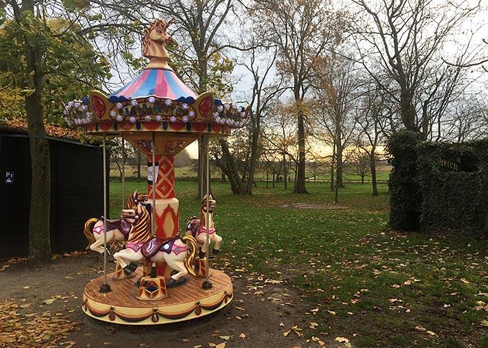 Kleines buntes Kinderkarussell mit Plastik-Pferden