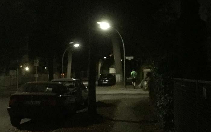 Läufer am frühen Morgen im Dunkeln auf einer spärlich beleuchteten Straße