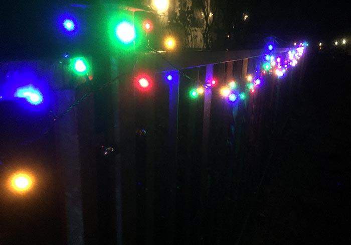 Weihnachtsbeleuchtung an einem Zaun