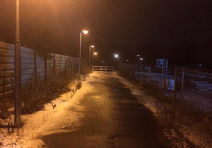 Von Laternen beleuchteter Weg entlang einer Baustelle mit etwas Schnee