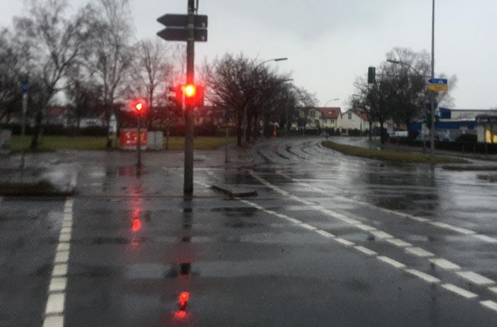 Straßenkreuzung im Regen, die Ampeln zeigen Rot