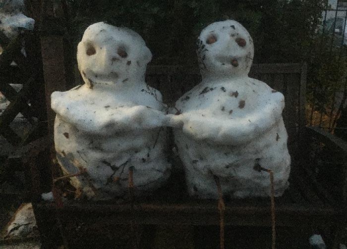 Schneemann-Paar auf einer Bank