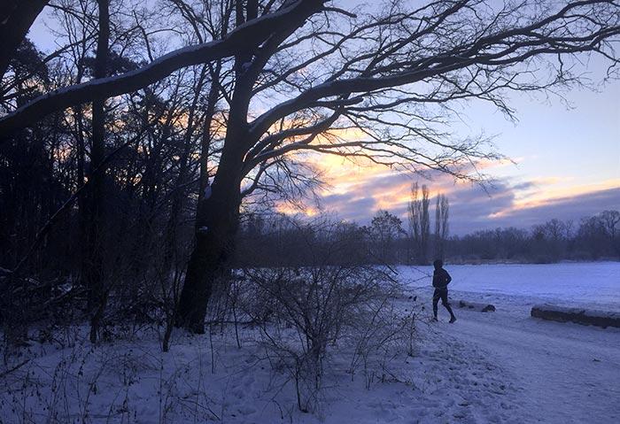 Läufer an schneebedecktem Feld, im Hintergrund ein schöner Sonnenaufgang