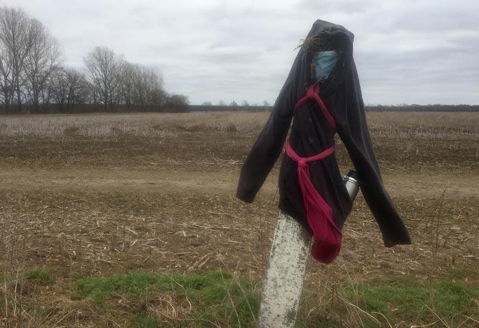 Pfeiler am Feldrand, der zu einer menschligen Figur verkleidet wurde: mit Jacke, Mundschutz und Thermoskanne in der Tasche