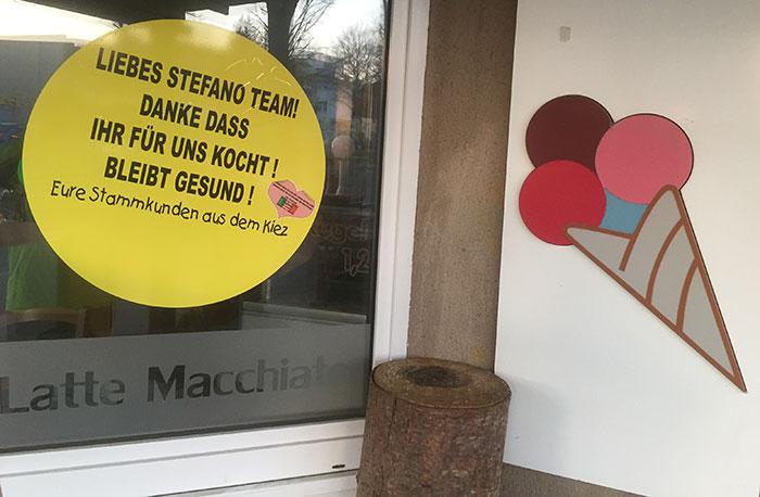 """Großer Aufkleber auf Restaurant-Fenster """"Liebes Stefano Team! Danke, dass ihr für uns kocht! Bleibt gesund!"""""""