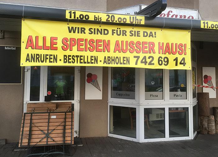 """Banner """"Alle Speisen außer Haus!"""" an einem Italienischen Restaurant"""