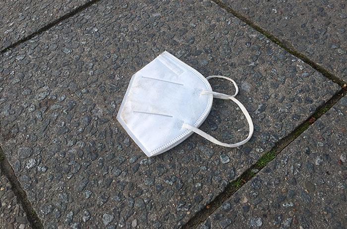 Weggeworfene weiße FFP2-Maske auf Gehweg