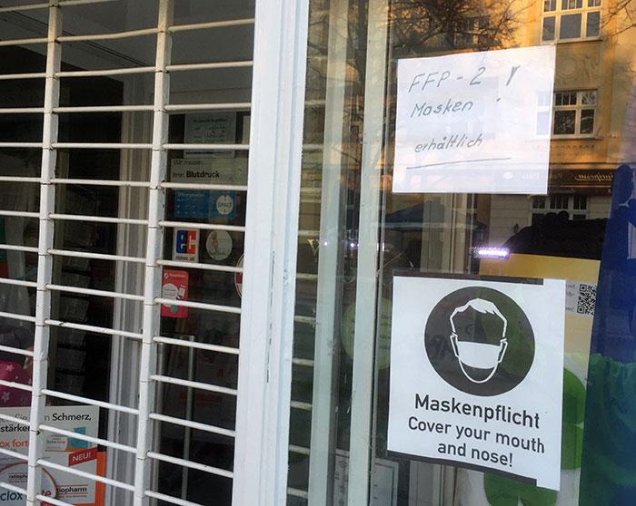 """Corona-Hinweise Maskenpflicht und """"FFP-2 Masken erhältlich!"""" an Apotheke"""