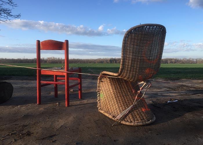 Ein roter Stuhl und ein Korbsessel, abgestellt am Feldrand
