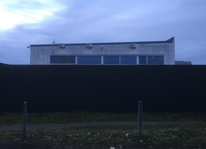 Firmengebäude, das knapp über die Grundstücksmauer ragt