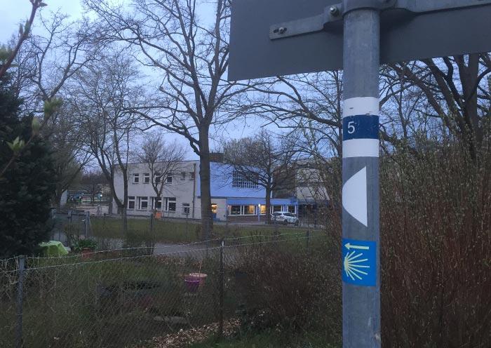 Schilderpfahl mit Aufklebern für Route 5 und den Jakobsweg