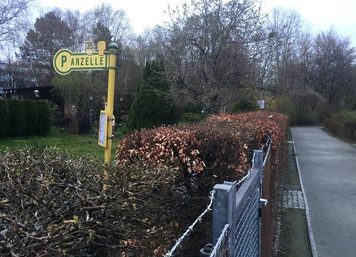"""Kleingarten mit altem gelben Haltestellenschild """"Parzelle"""""""