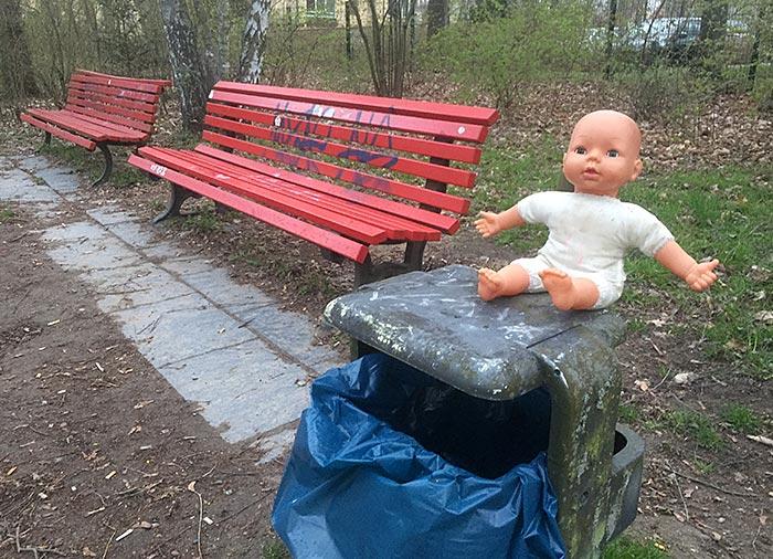 Zwei rote Parkbänke, im Vordergrund eine Babypuppe auf einem Abfallkorb sitzend