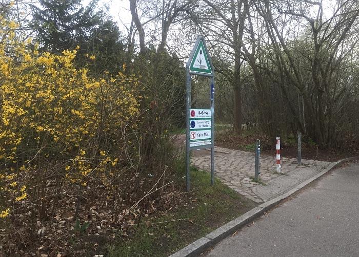 Beginn einer Parkanlage, im Vordergrund gelb blühende Forsythien