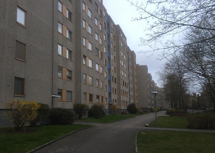 Graue 7-stöckige Wohngebäude mit gelb-orange abgesetzten Fenstern
