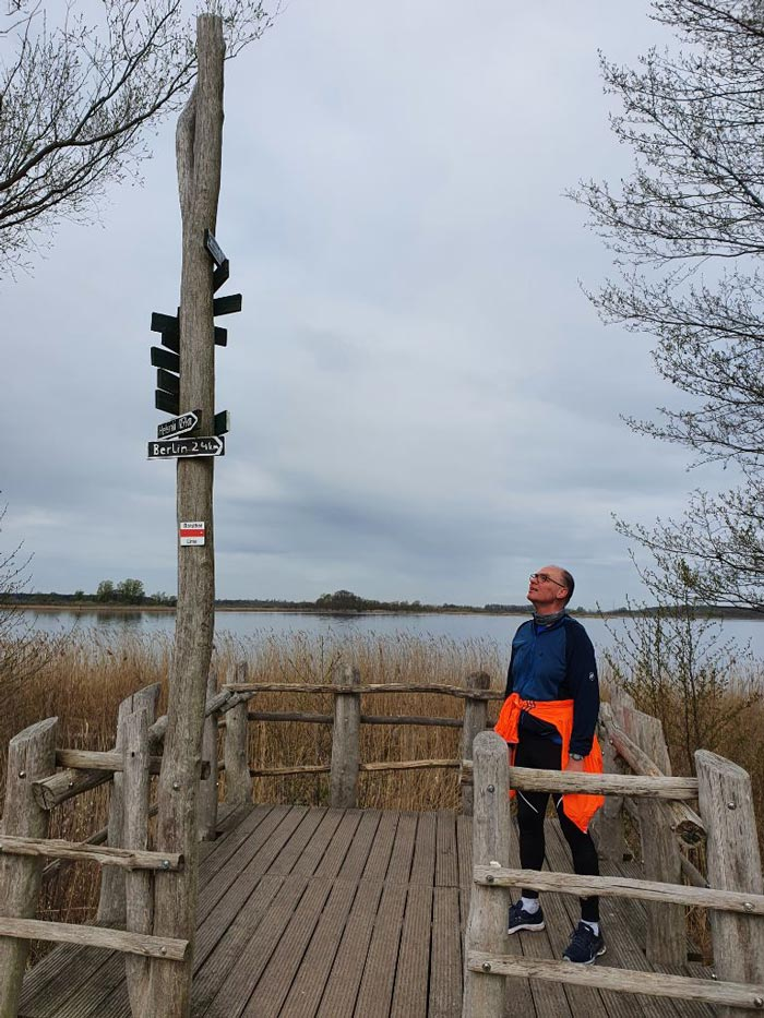 """Läufer sieht an einem Hinweispfahl mit Schild """"Berlin 24 km"""" auf"""