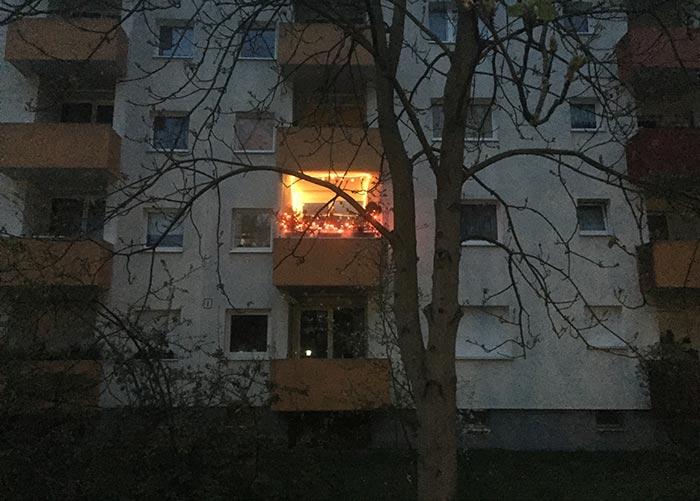 Wohnblock im Halbdunkel, nur ein Balkon ist hell erleuchtet